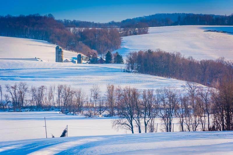 Vista de los campos y de las casas nevados de granja en el condado de York rural foto de archivo libre de regalías