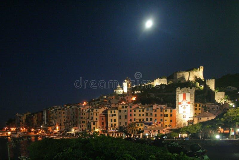 Vista de los edificios del ` s de Portovenere en la noche debajo de la luna con un castillo, una torre y una catedral iluminados imagen de archivo