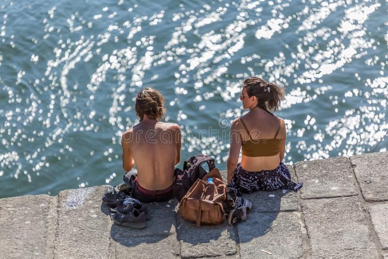 Vista de los pares que se sientan en muelles en el río del Duero, tomando el sol y disfrutando de la visión fotos de archivo libres de regalías