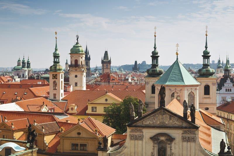 Vista de los tejados de Praga, con los tejados tejados rojos y las estatuas, fotos de archivo