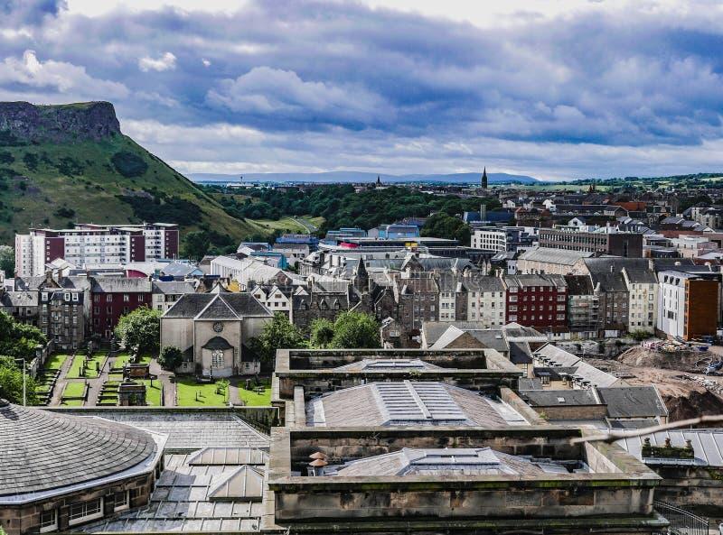 Vista de los tejados de Edimburgo con los riscos de Salisbury en el fondo imagenes de archivo