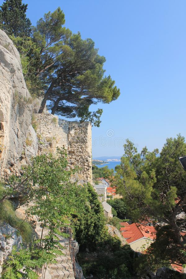 Vista de los tejados rojos del centro histórico de Omis Croacia contra el mar fotos de archivo