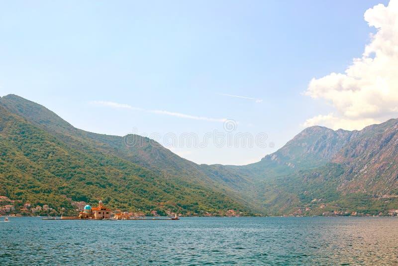Vista de montañas enselvadas verdes y mar azul, cielo azul y nubes blancas fotos de archivo
