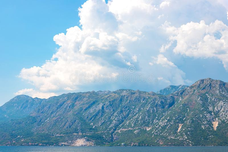 Vista de montañas enselvadas verdes y mar azul, cielo azul y nubes blancas fotografía de archivo