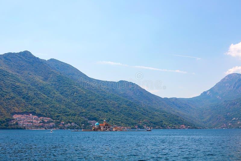 Vista de montañas enselvadas verdes y mar azul, cielo azul y nubes blancas imagen de archivo