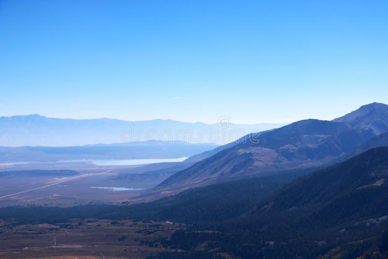 Vista de montañas por una mañana de niebla contra un cielo azul foto de archivo libre de regalías