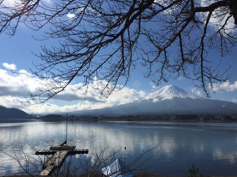 Vista de Mt Fuji con el cielo azul claro, las nubes y el lago liso emergen en invierno en Kawaguchiko, Yamanashi, Japón fotografía de archivo libre de regalías