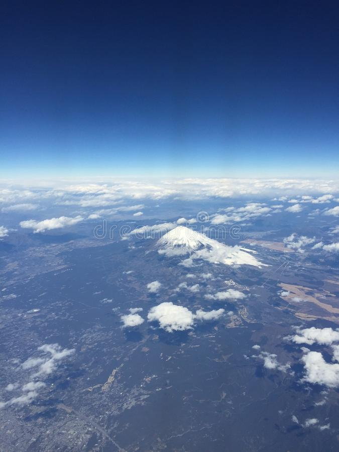 Vista de Mt Fuji con el cielo azul y las nubes claros, fuera de la ventana plana al dirigir a Hong Kong foto de archivo libre de regalías