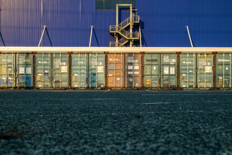 Vista de muchas puertas de los contenedores con el fondo de la salida de incendios imagenes de archivo
