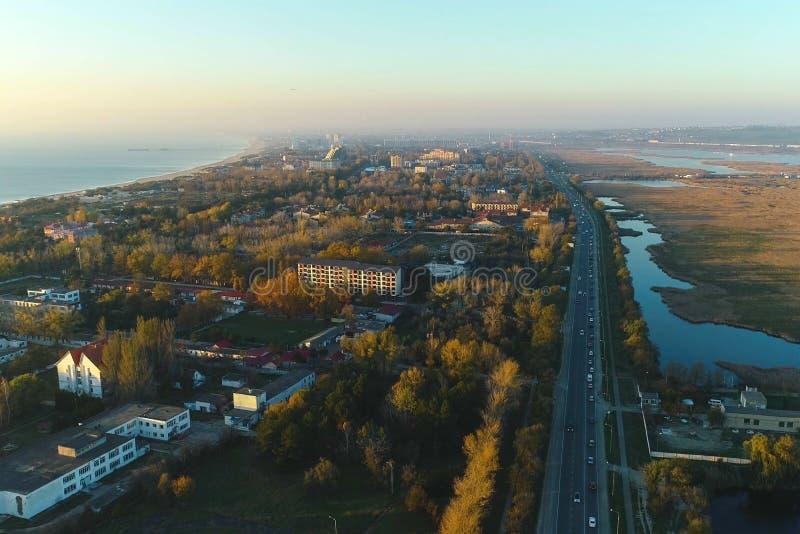 Vista de nivelamento bonita da cidade litoral com estrada e os prados molhados Foto aérea imagens de stock