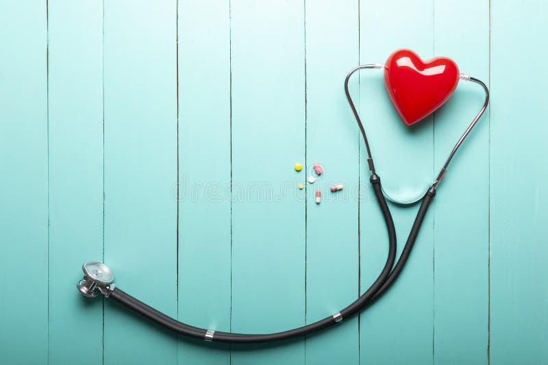 Vista de Op. Sys. de estetoscopios, del modelo rojo del corazón y de drogas en el escritorio de madera verde, escritorio del func fotografía de archivo libre de regalías
