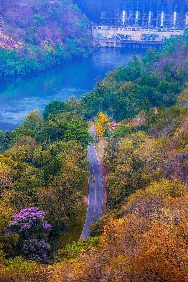 Vista de pájaro del camino del asfalto en la más forrest mezclado y de hojas caducas del otoño con la presa en la cima del paisaj imagen de archivo