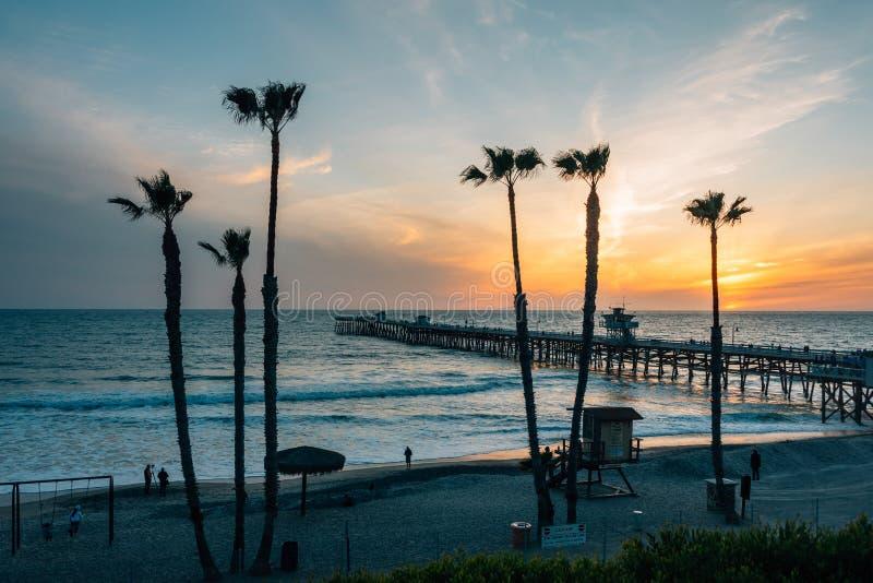 Vista de palmeras, de la playa, y del embarcadero en la puesta del sol, en San Clemente, Condado de Orange, California fotografía de archivo libre de regalías