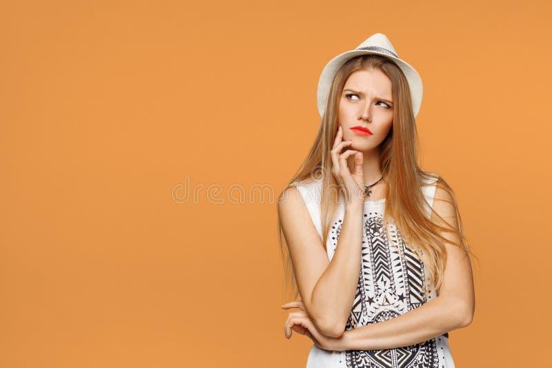 Vista de pensamento da mulher bonita nova ao lado no espaço vazio da cópia, sobre o fundo alaranjado imagem de stock