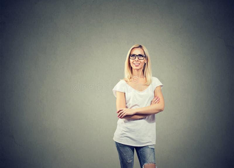 Vista de pensamento da mulher feliz acima ao estar perto de um muro de cimento foto de stock royalty free