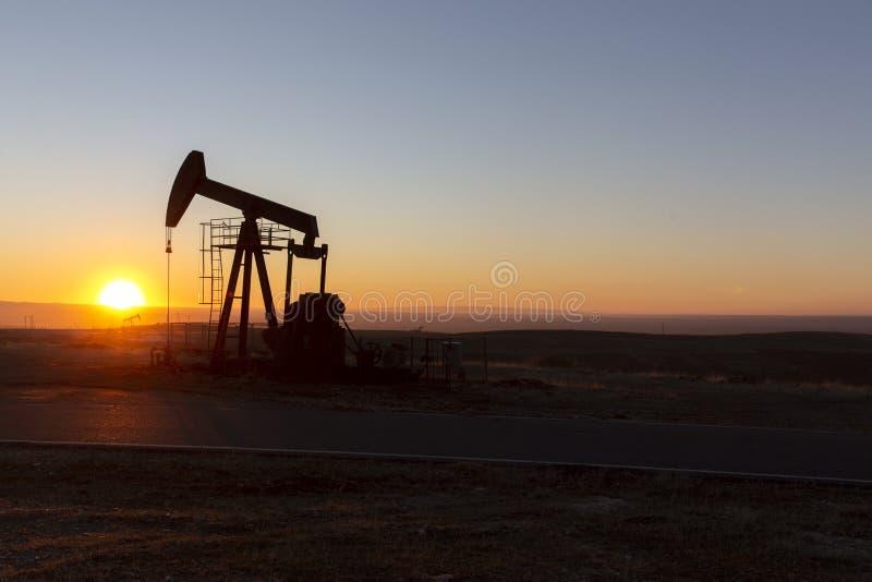 Vista de Pumpjack no por do sol da área do petróleo fotografia de stock royalty free