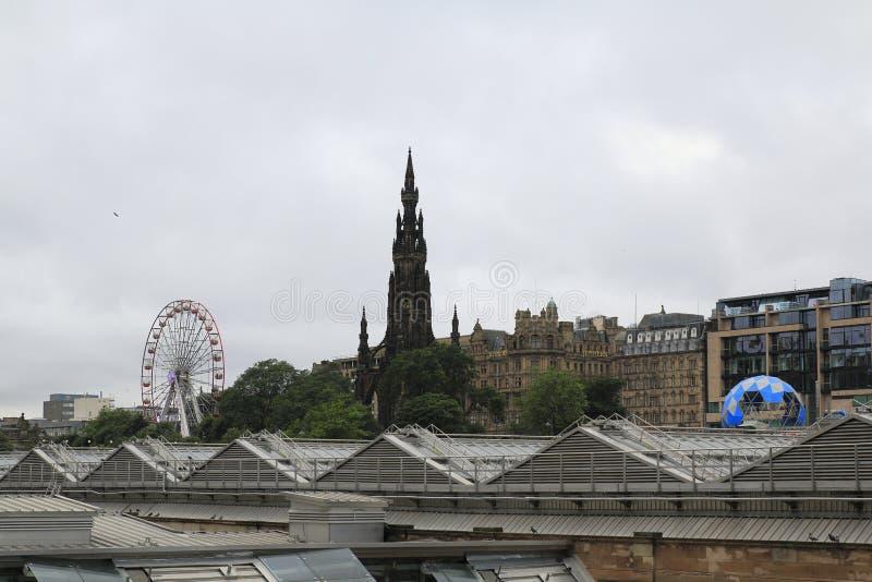 Vista de Scott Monument e da cidade velha com Ferris Wheel, no festival público da franja, Edimburgo Escócia imagem de stock royalty free