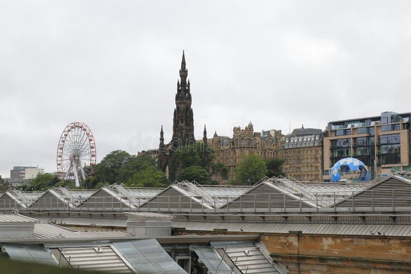 Vista de Scott Monument e da cidade velha com Ferris Wheel, no festival público da franja, Edimburgo Escócia fotos de stock