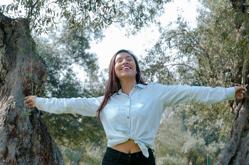 Vista de sorriso da mulher acima ao céu azul que toma a respiração profunda que comemora a liberdade Expressão humana positiva da foto de stock royalty free