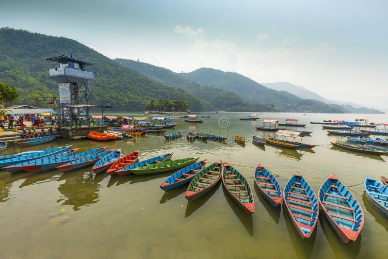 Vista de surpresa no lago Phewa os barcos coloridos param no enfileirado um meio-dia imagens de stock