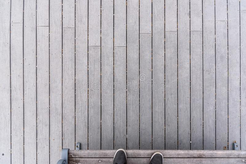 Vista de tablones de madera grises en paseo marítimo con los pies en banco imagen de archivo libre de regalías