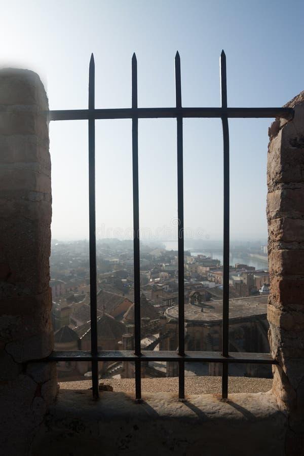 Vista de Tortosa con la catedral a través de las barras del Sudacastl imagen de archivo libre de regalías