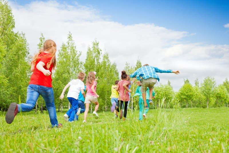 Vista de trás das crianças que correm através do campo fotografia de stock