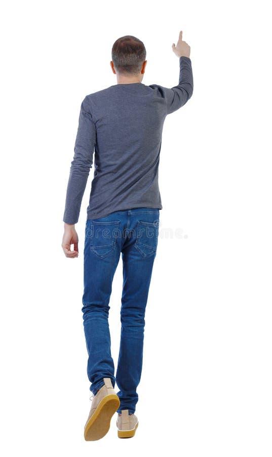 Vista de trás de um homem andando com uma mão apontada imagens de stock royalty free