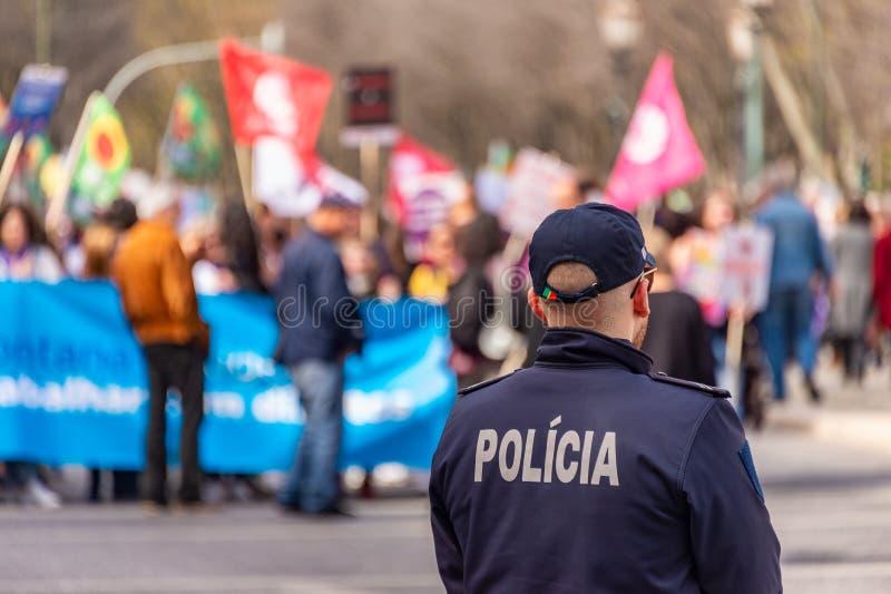 Vista de trás de um policial durante um protesto em Lisboa, Portugal imagens de stock