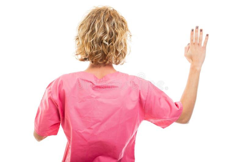 Vista de trás de uma jovem enfermeira usando uma esfregona rosa fazendo juramento fotografia de stock