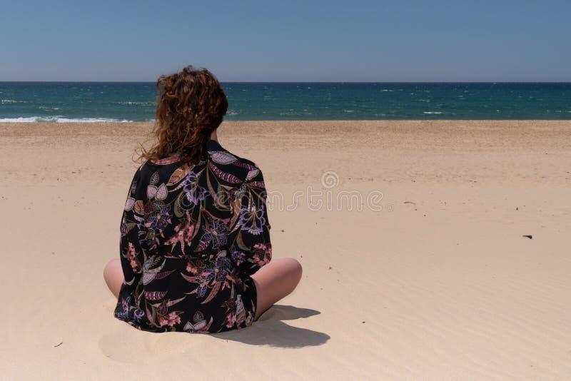 Vista de trás de uma mulher meditando praticando ioga na praia foto de stock