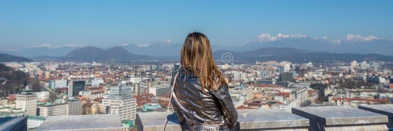 Vista de trás de uma posição da mulher sobre o castelo de Ljubljana fotos de stock royalty free