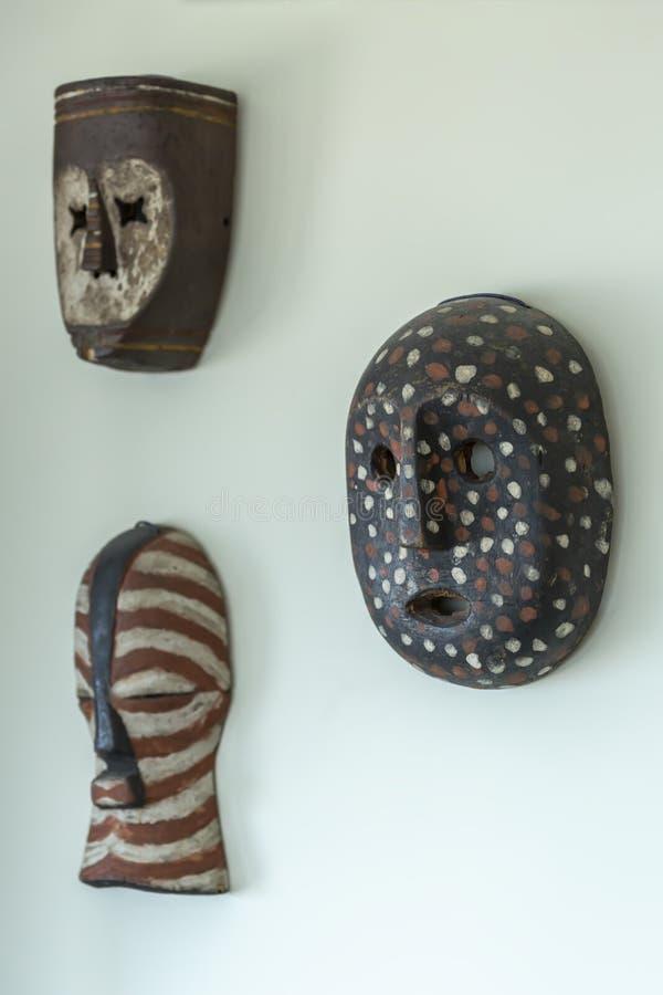 Vista de tres máscaras de madera decorativas, moldeada y pintada a mano, en la pared de la casa imagen de archivo