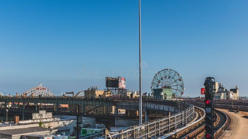 Vista de trilhas do trem do metro e roda e montanhas russas de ferris sob o céu azul em Coney Island imagem de stock royalty free