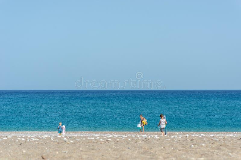 Vista de um distante da mãe e das duas crianças que estabelecem seu lugar em uma praia foto de stock royalty free