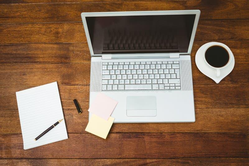 Vista de um portátil cinzento com café imagem de stock