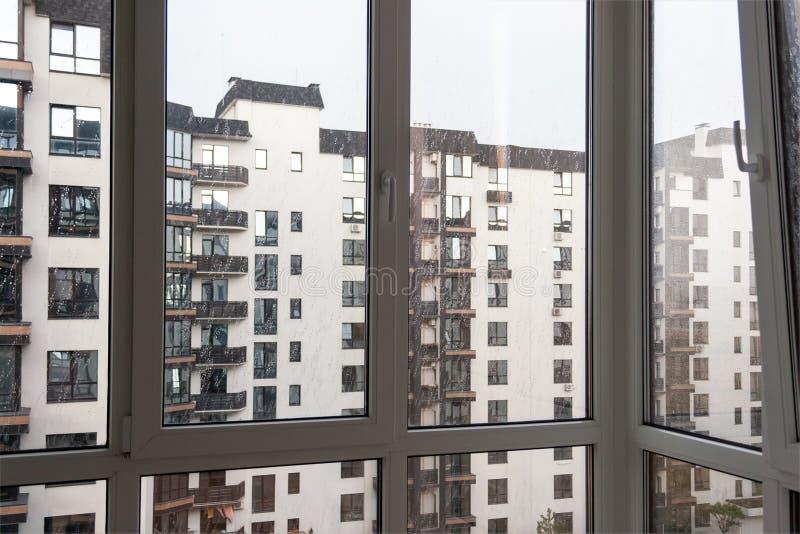 Vista de um prédio de apartamentos vizinho com os balcões marrons através da janela panorâmico branca em um dia nebuloso chuvoso imagens de stock royalty free