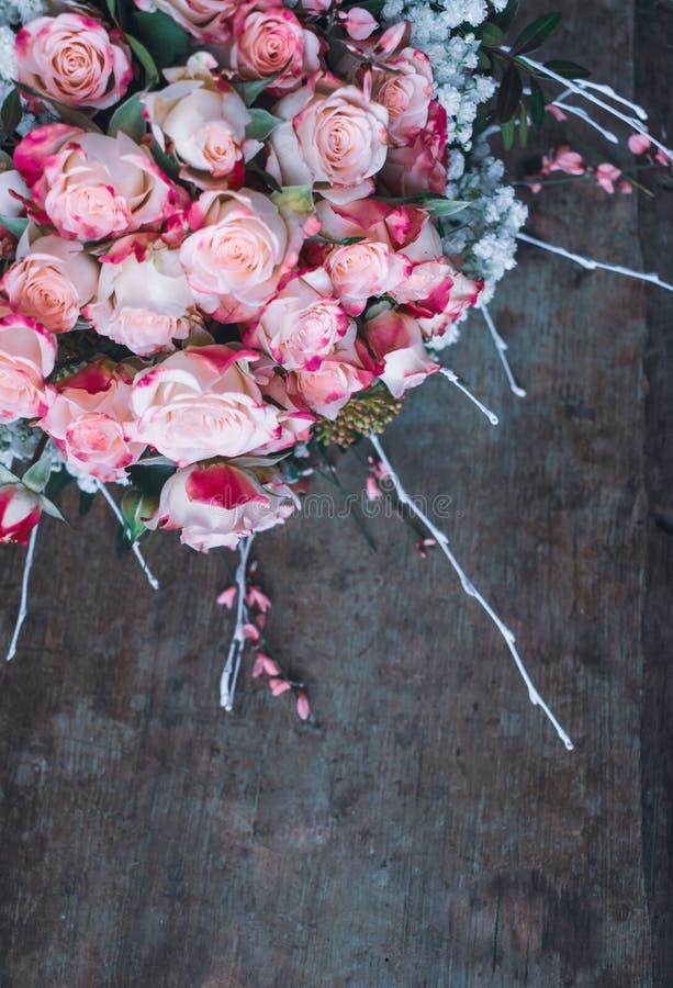 Vista de um ramalhete de rosas cor-de-rosa pasteis frescas com em fundo de madeira rústico imagem de stock