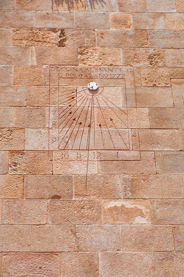 Vista de um relógio de sol velho situado em uma parede antiga Números romanos escritos na placa retangular imagem de stock