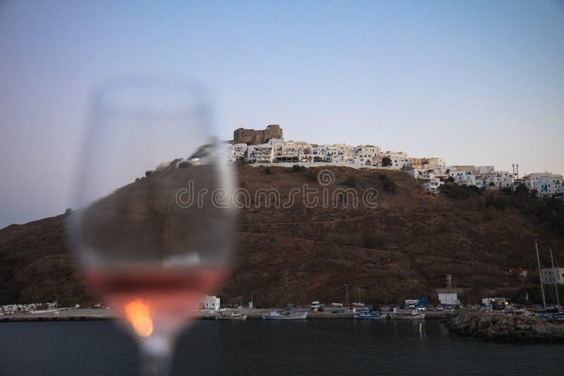 Vista de um vidro de vinho contra um marco em uma ilha grega fotos de stock royalty free