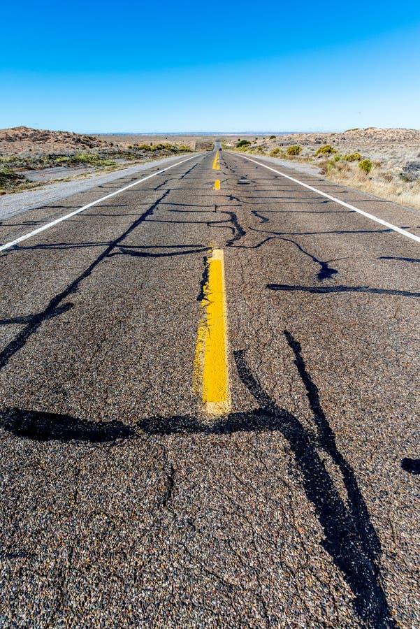 Vista de uma estrada reta infinita que corre através do deserto imagens de stock royalty free