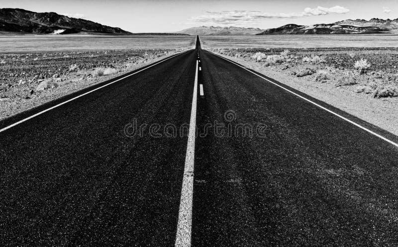 Vista de uma estrada reta infinita que corre através do deserto fotografia de stock