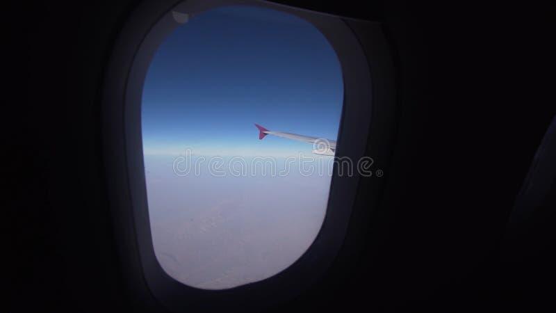 Vista de uma janela do avião em montanhas fotografia de stock