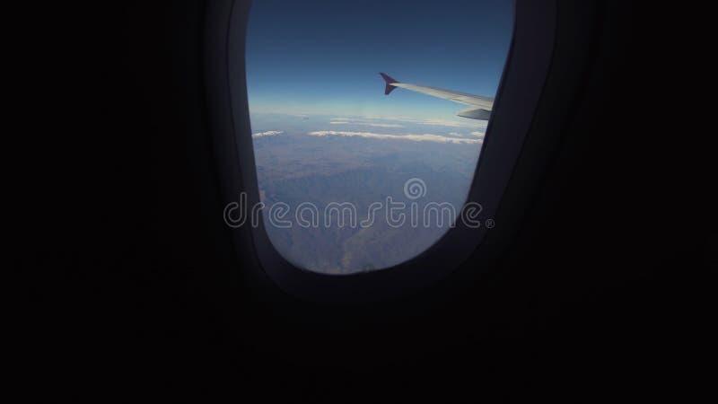 Vista de uma janela do avião em montanhas foto de stock