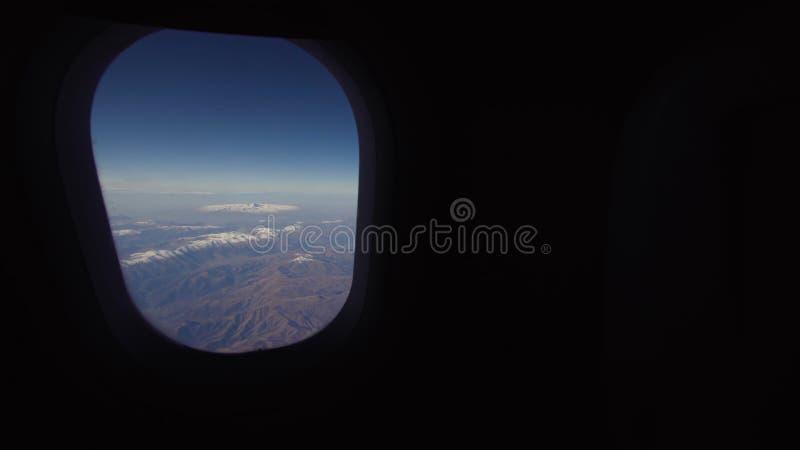 Vista de uma janela do avião em montanhas imagens de stock royalty free