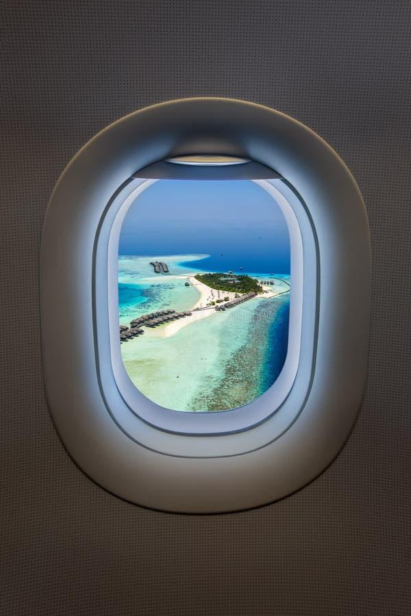 Vista de uma janela do avião a uma ilha tropical do paraíso em Maldivas foto de stock