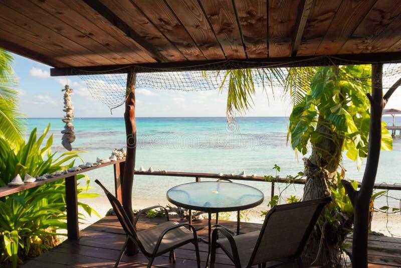 Vista de uma lagoa tropical azul do convés de madeira de um bangalô com uma mesa e cadeiras e enquadrada por palmeiras e conchas fotografia de stock royalty free