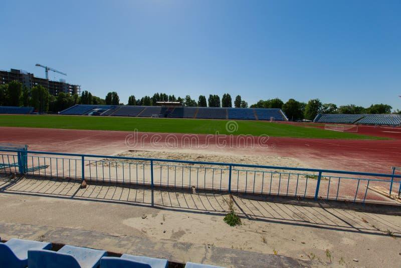 Vista de uma pista de atletismo vermelha e um estádio com um fie da grama verde foto de stock