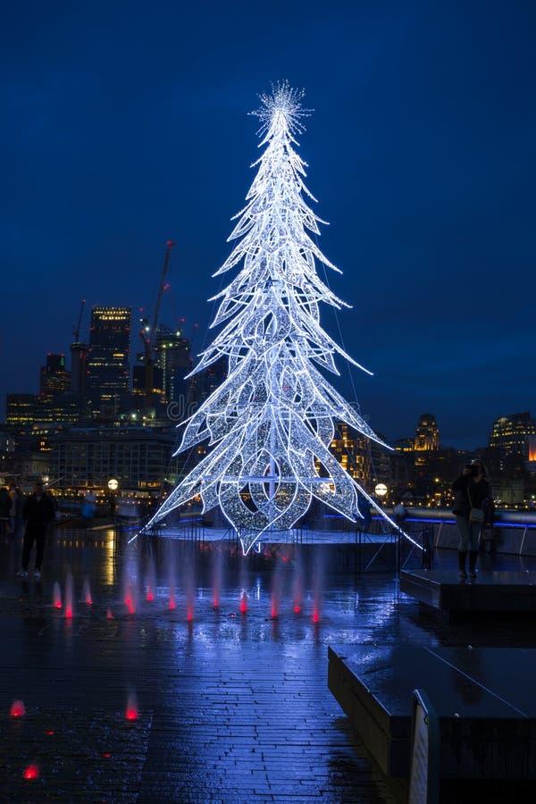 Vista de un árbol de navidad moderno del LED que se coloca al lado de la ciudad H fotografía de archivo