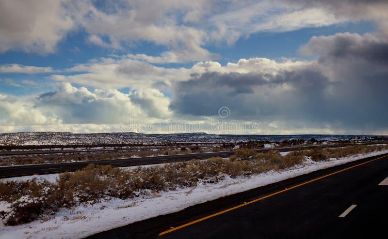 Vista de un camino que curva cubierto en el camino durante invierno, montañas de la manera de la nieve de la nieve en la distanci imagen de archivo libre de regalías